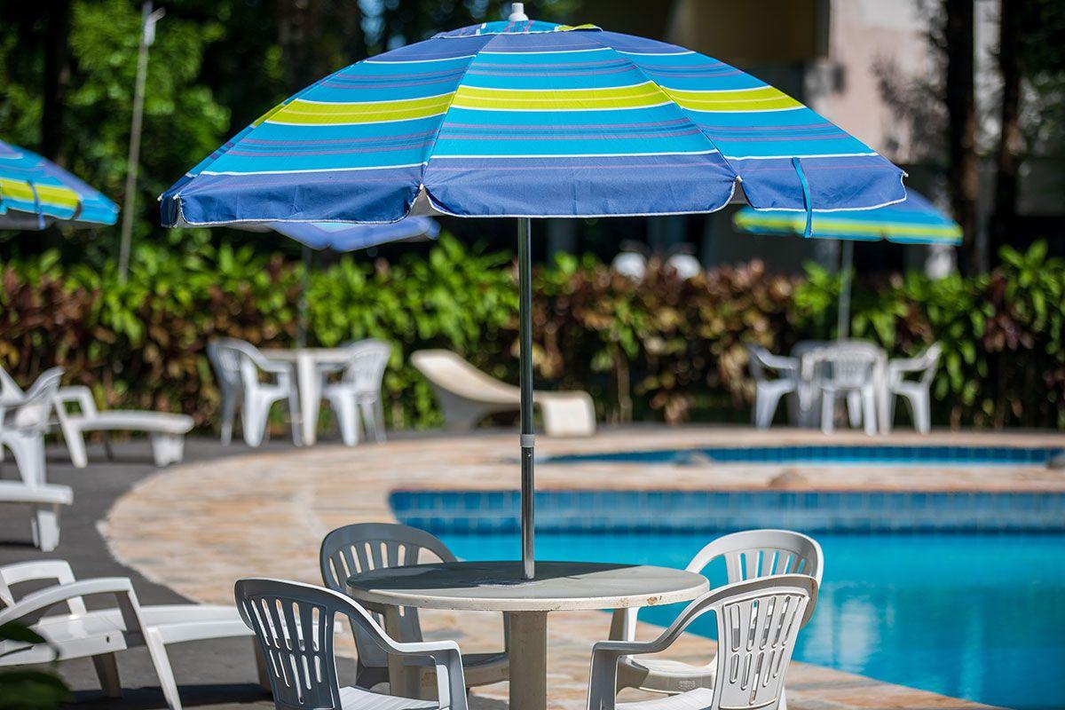 Mesas com guarda-sol na piscina